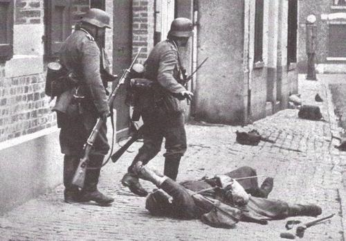 German infantry advance past wounded French soldier.jpg